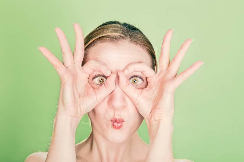 Woman with hands on eyes forming OK sign